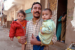 CAIRO, EGYPT- DECEMBER 4, 2004 : A father brings his children in the street as health workers immunize children under five against polio during the national door to door polio vaccination campaign in Giza district near Cairo, on December 4, 2005. Egypt remains one of the 6 polio endemic countries in the world, with one case in 2004. (Photo by Jean-Marc Giboux/Getty Images)