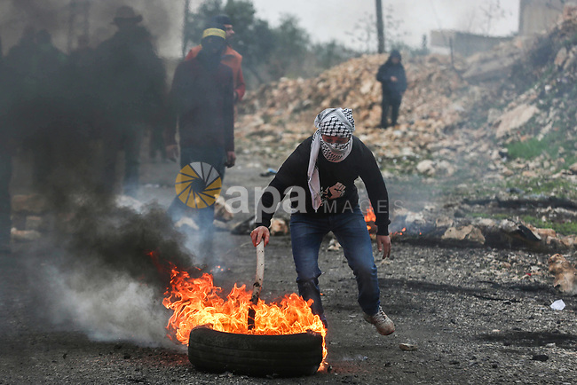 A Palestinian protester carry flaming tires during clashes with Israel security forces following a weekly demonstration against the expropriation of Palestinian land by Israel in the village of Kfar Qaddum, near the West Bank city of Nablus on January 17, 2020. Photo by Shadi Jarar'ah