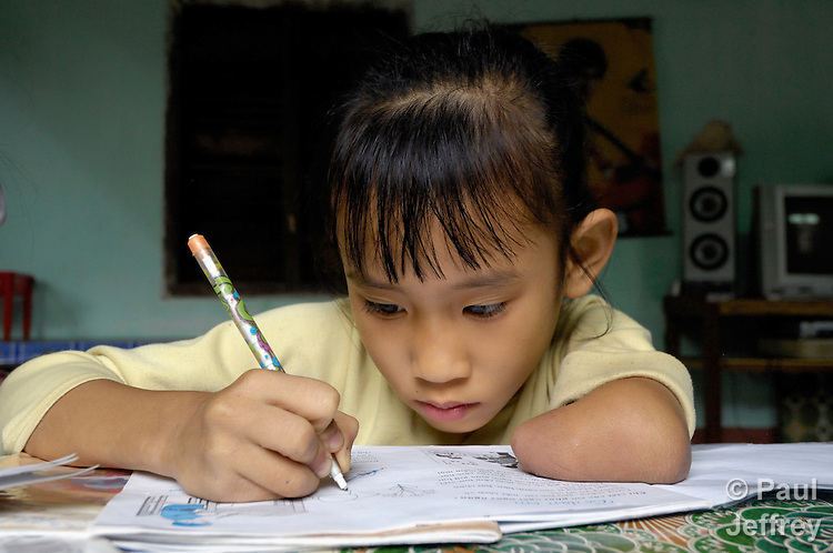 Luong Hoai Thuong does her homework. She was born without her left hand, a birth defect caused by Agent Orange remaining from the U.S. war against Vietnam. During the Vietnam War, US forces sprayed Agent Orange over forests and farmland in an attempt to deprive Viet Cong guerrillas of cover and food. The dioxin compound used in the defoliant is a long-acting toxin that can be passed down genetically, so it is still having an impact forty years on. The Vietnam Red Cross estimates that some 150,000 Vietnamese children are disabled owing to their parents' exposure to the dioxin. Symptoms range from diabetes and heart disease to physical and learning disabilities.
