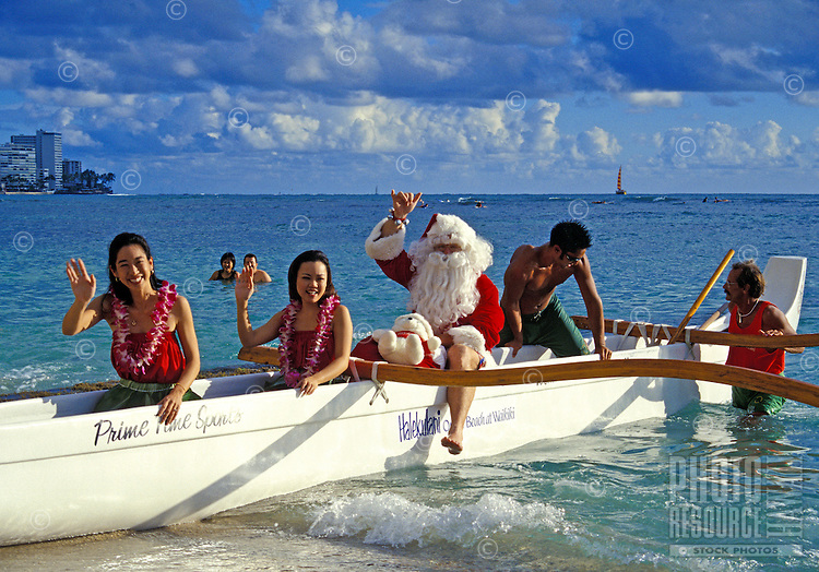 Santa arrives by outrigger canoe on Christmas Eve on Waikiki Beach with his hula girl helpers.