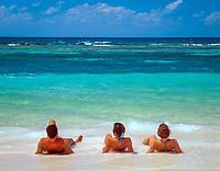 Dominikanische Republik, Isla Saona, Laguna Canto de la Playa, Strand, Mann und zwei junge Frauen liegen im Sand im Wasser   Dominican Republic, Saona Island, Laguna Canto de la Playa, beach, man and two young women lying in the sand and water