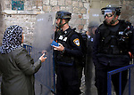 """Israeli police check Palestinian women's IDs and bags outside the Al-Aqsa mosque compound in the Old City of Jerusalem on April 16, 2014. Dozens of Palestinians were wounded in clashes with Israeli police that erupted when Jerusalem's flashpoint Al-Aqsa mosque compound was opened to Jewish visitors. Palestinians threw """"stones and firecrackers"""" at police when they opened the walled compound's gates and Israeli police responded with stun grenades and rubber-coated bullets, they closed the complex to the Jewish visitors after a small number had toured the site. Photo by Saeed Qaq"""