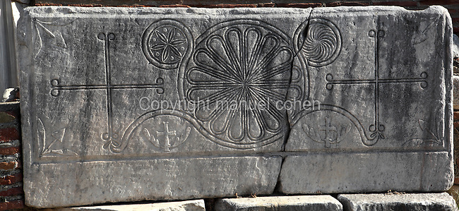 "Decorative Christian carving showing 2 crosses with floral motifs in circles and smaller winged crosses below, from the nave of the Basilica of St John, built 536-565 AD under Emperor Justinian on the site of the apostle's tomb, Ephesus, Izmir, Turkey. St John the Evangelist spent his last years in Ephesus and died here. In the 4th century a church was erected over his tomb but in the 6th century Justinian ordered the construction of a large, 6-domed basilica built of stone and brick with marble columns in a Greek cross plan, the ruins of which we see today. The church measures 130x56m and was an important Christian pilgrimage site, attaining the status of ""Church of the Cross"". Originally, the church interior would have been covered with frescoes, and the vaults with mosaics. An earthquake in the 14th century destroyed most of the building. Ephesus was an ancient Greek city founded in the 10th century BC, and later a major Roman city, on the Ionian coast near present day Selcuk. Picture by Manuel Cohen"