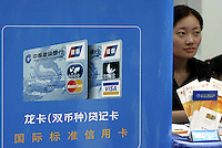 QS040502Shanghai015 20040502 SHANGHAI, CHINA: A saleswoman sits beside a credit card advertisement in Shanghai, China.