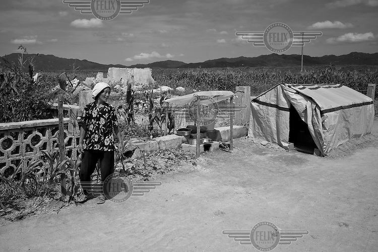 A woman photographed by a temporary tarpaulin shelter in Pongchon county, DPRK during a field visit by national and international Red Cross officials on Saturday August 27 2011. Consecutive floods caused by heavy rainfall and strong winds, together with the impact of typhoon Muifa which struck in early August, resulted in the destruction or severe damage of over 9,500 houses, rendering more than 25,000 people homeless between June 23 and August 9, according to data provided by the DPRK government. While flood damage was reported throughout the country, south and north Hwanghae provinces have been worst hit by the repeated flooding, leaving an already vulnerable population in a critical condition.  Photo by Morten Hvaal/Felix Features for IFRC.