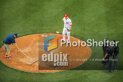 14 May 2016: Washington Nationals pitcher Shawn Kelley watches as a grounds crewman tends to the mound in the rain as umpires converse during a delay in the first game of a double-header against the Miami Marlins at Nationals Park in Washington, DC. The Nationals defeated the Marlins 6-4 in the afternoon matchup.  Mandatory Credit: Ed Wolfstein Photo *** RAW (NEF) Image File Available ***
