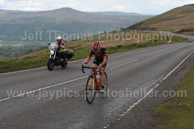 PRO team cyclists near the top of the challenging iconic and notorious 6km 10% stretch of road namely The Tumble during the Wales Velothon 2016 140km route cycling race. A lone competitor alongside a control motorcycle.  <br />