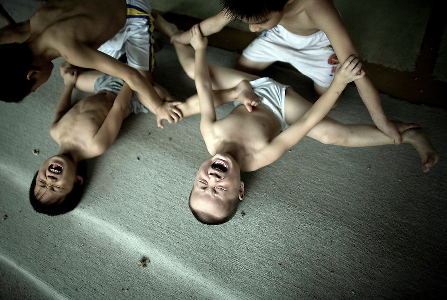 Chinese children scream as their legs are stretched during a training session in a gymnastics school in Xiantao, in Hubei province