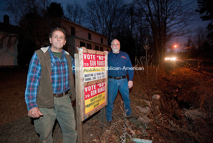 PLYMOUTH, CT--- -121515JS03--Plymouth resident George Porter, Jr, left, and business owner Charles Cronin, Jr., owner of C &amp; C Hydraulics, Inc., right, stand at a home across the street from a proposed gun range on Wolcott Road in Plymouth. They are two of the many local residents opposed to the range. Their opposition is not about guns, but with safety, the noise and how it would affect property values. <br /> Jim Shannon Republican-American