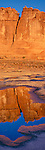 Arches National Park, UT: The Organ stands in morning sun with reflections in vernal slick rock pools near Courthouse Wash