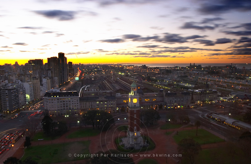 A bird's eye view over the city at sunset. In the foreground the Retiro train station and the Torre de los Ingleses or torre monumental. Buenos Aires Argentina, South America