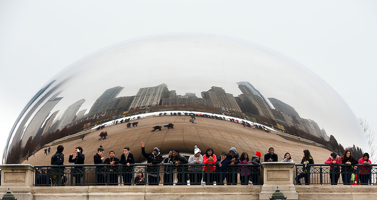 Chicago holiday scenes:  Tourists gather in the shadow of the &quot;Cloud Gate&quot; sculpture, a.k.a. &quot;The Bean&quot;, to watch folks ice skate at the McCormick Tribune Ice Rink in Millennium Park on Michigan Ave. <br /> <br /> (Optional Trim: Cloud Gate is British artist Anish Kapoor's first public outdoor work installed in the United States. <br /> <br /> The 110-ton elliptical sculpture is forged of a seamless series of highly polished stainless steel plates, which reflect Chicago&rsquo;s famous skyline and the clouds above. A 12-foot-high arch provides a &quot;gate&quot; to the concave chamber beneath the sculpture, inviting visitors to touch its mirror-like surface and see their image reflected back from a variety of perspectives. <br /> <br /> Inspired by liquid mercury, the sculpture is among the largest of its kind in the world, measuring 66-feet long by 33-feet high. ) (Photo by Jamie Moncrief)