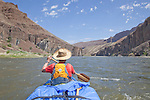 Robbie Scott paddles in the bow of a canoe in the John Day River Canyon.  Clarno to Cottonwood Bridge section.  A spray cover is used.  Cliffs are of basalt, an igneous rock.