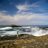 A Person looking through Binoculars and watching for Whales along the Rugged Pacific Coastline near Tofino, on West Coast of Vancouver Island, BC, British Columbia, Canada (Model Released)