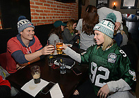 From left, Ryan Turgeon, a Patriots fan and his wife Patti Turgeon of Moorestown, New Jersey, an Eagles fan, have a drink at Smith's Bar & Restaurant Sunday, February 04, 2018 in Philadelphia, Pennsylvania. The two were married six months ago and hope that they will still be friends after the Super Bowl. Generally a Patriots hangout, the bar was overridden by Eagles fans singing the Eagles fight song. WILLIAM THOMAS CAIN / For The Inquirer