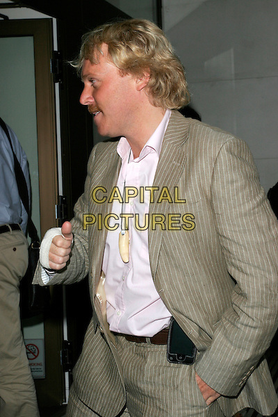 LEIGH FRANCIS - AVID MERRION.ITV2 Autumn Launch Party, The Roof Gardens, London, England..August 19th, 2008.half length beige pinstripe suit bandage injury wound hand in pocket profile moustache mustache facial hair mobile phone iphone .CAP/AH.©Adam Houghton/Capital Pictures.