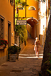 A woman stops to look at the view while walking down a path between houses in Varenna, Italy on Lake Como