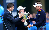 Matthew Fitzpatrick of England receives the trophy from Ian Poulter following his victory during Round 4 of the 2015 British Masters at the Marquess Course, Woburn, in Bedfordshire, England on 11/10/15.<br /> Picture: Richard Martin-Roberts | Golffile