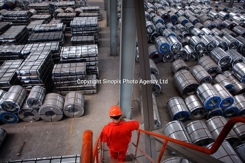 A worker walks down a flight of stairs onto a floor filled with steel products at a warehouse run by the Shanghai Yirong Trading Company Ltd in Shanghai, China..10 Apr 2009