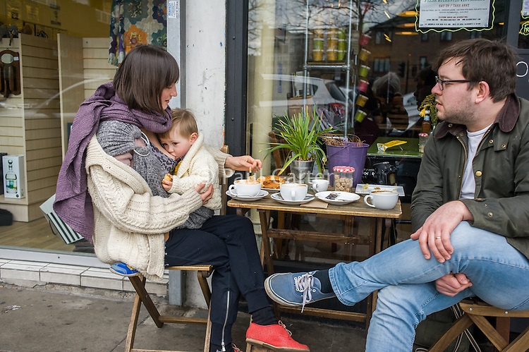 A mother breastfeeds her 15 month old boy who is in a sling and holding a piece of bread. She is talking to her partner across the table.<br /> <br /> London, England, UK<br /> 22-03-2015<br /> <br /> © Paul Carter / wdiip.co.uk