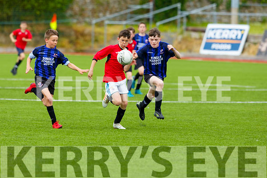 Tralee Dynamos Evan Quilligan keeps his eye on the ball dispite the close attention from Dingle Bay Rovers Paddy Ryan and Alex Buchanan in the U13 Schoolboys Shield Final in Mounthawk Park on Saturday