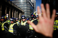 Riot police are seen behind a student protestor's raised hand shortly after a baton charge outside the Bank of England. Thousands of protestors descended on the City of London ahead of the G20 summit of world leaders to express anger at the economic crisis, which many blame on the excesses of capitalism.