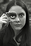 A young woman holding a picture of her eye infront of her face