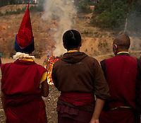 Buddhist monks chanting prayers during the Losar New Year ceremonial bonfire at a monastery in the Himalayan foothills of Sikkim, India