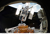 In Earth Orbit - May 19, 2009 -- The space shuttle Atlantis' remote manipulator system arm lifts the Hubble Space Telescope from the cargo bay and is moments away from releasing the orbital observatory to start it on its way back home to observe the universe, in this image taken on May 19, 2009..Credit: NASA via CNP