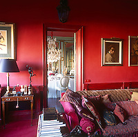 A country house sitting room decorated in bold shades of red and fuschia pink. A comfortable sofa is piled with cushions and throws. A lamp stands on a Georgian side table next to an open door that gives a view to an opulent dining room beyond.