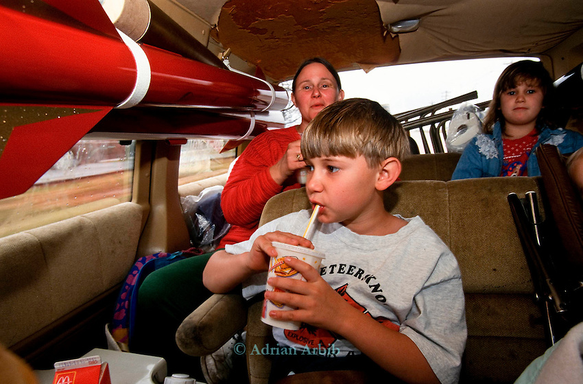 A family make  their way  to an amateur rocketery  festival  .Manchester, Tennessee.