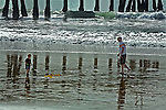 Father and three year old blonde son play in ocean near pilings of Santa Monica pier