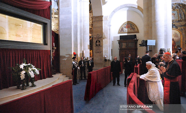 "Pope Benedict XVI (R) blesses the audience in front of the Shroud in the Turin cathedral on May 2, 2010. Pope Benedict XVI will bow before the Shroud of Turin, the object of both bafflement and veneration believed by many to be the burial cloth of Jesus Christ. ""It will be a propitious occasion to contemplate this mysterious visage that speaks silently to the heart of men, inviting them to recognise the face of God,"" Benedict said in 2008 as he announced the planned new exposition of the mysterious cloth. The 83-year-old pontiff, in his one day visit in Turin, will celebrate an open-air mass in Piazza San Carlo next to the Turin Cathedral housing the shroud, meetings with youths and a visit to a centre for severely handicapped people"