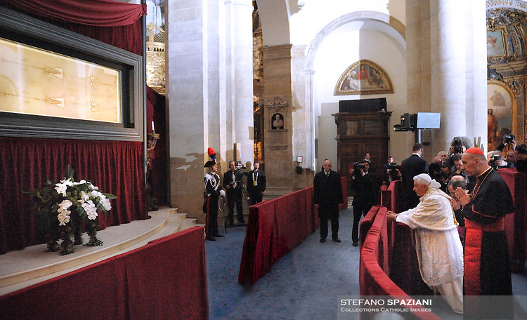 """Pope Benedict XVI (R) blesses the audience in front of the Shroud in the Turin cathedral on May 2, 2010. Pope Benedict XVI will bow before the Shroud of Turin, the object of both bafflement and veneration believed by many to be the burial cloth of Jesus Christ. """"It will be a propitious occasion to contemplate this mysterious visage that speaks silently to the heart of men, inviting them to recognise the face of God,"""" Benedict said in 2008 as he announced the planned new exposition of the mysterious cloth. The 83-year-old pontiff, in his one day visit in Turin, will celebrate an open-air mass in Piazza San Carlo next to the Turin Cathedral housing the shroud, meetings with youths and a visit to a centre for severely handicapped people"""