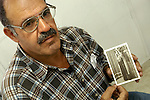 Adel Samara holds a photo of his wife Enayeh, a Palestinian-US citizen, in the West Bank city of Ramallah. Enayeh, living in Chicago, is not permitted to visit Israel.<br />