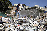 Shaker Ja'abis (L) walks on the rubble of his own home after demolishing it by bulldozer in Jabel Mukaber neighborhood southern Jerusalem on Sep 05, 2013. Ja'abis decided to demolish his own home to carry out an Israeli court order under the pretext of building without municipality permit. Many Palestinians end up demolishing their homes themselves to avoid the high cost of paying for Israeli government bulldozers, or being sent to prison for not being able to pay. Photo by Saeed Qaq