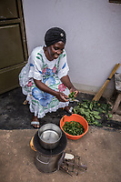 Uganda, Bujuuko. Jalia Musoke runs a tree farm and sewing business. She is busy with work and chores and uses a BioLite wood cook stove that she feels is faster than a regular cookstove. At home using her cookstove.