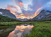 Wind River Range, WY: A colorful sunset and reflections in the North Fork of the Popo Agie River with the profile of the Cirque of the Towers and Lizard Head in the distance; Bridger Wilderness in the Bridger National Forest in summer