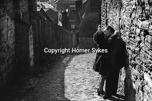 Middle age couple kiss in a back alley Durham, Yorkshire 1974