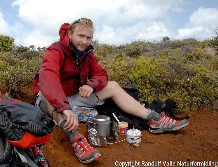 Gutt spiser mat i North Cape Scientific reserve, helt nord på New Zealand. ---- Man eating in North Cape Scientific reserve at the northern point of New Zealand.