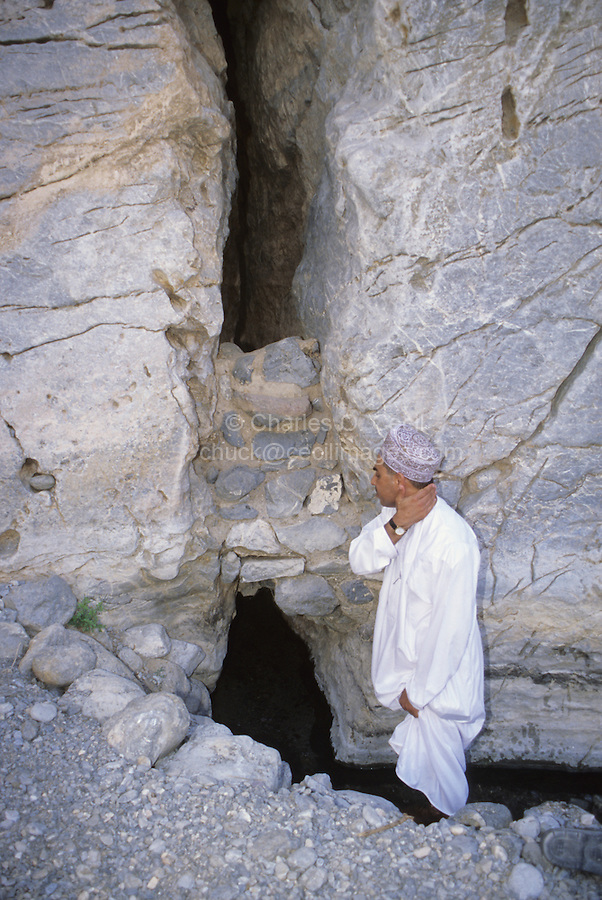 Wadi Bani Kharus, Oman, Arabian Peninsula, Middle East - Water from the Rock.  An Omani refreshes himself with cool water issuing from a cleft in the rock in the narrow mountain valley of Wadi Bani Kharus.  Water from such springs flows by gravity through a series of canals and channels, called aflaj (singular, falaj), to terraced gardens farther down the mountain valley.