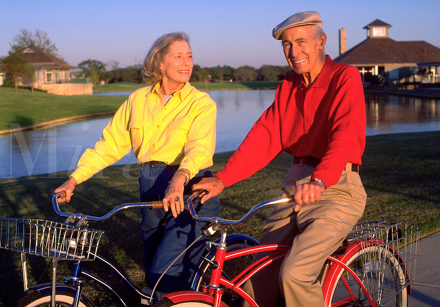 retired elderly couple riding bikes together in an upscale neighborhood park with a lake in the background. Jene and Ray. United States residential park.