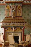 A religious statue is flanked by a pair of painted angels above an ornate mantelpiece in this sitting room with walls decorated with hand-painted initials