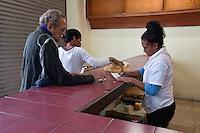 Cuba, Havana.  Cubans Buying Bread.  Sales Clerk Signing Ration Book.