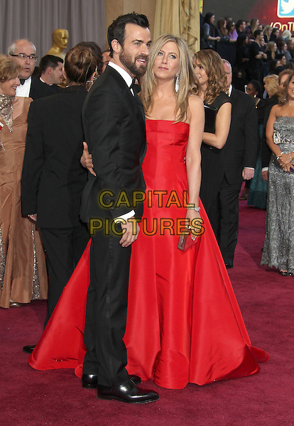 Justin Theroux & Jennifer Aniston (wearing Valentino).85th Annual Academy Awards held at the Dolby Theatre at Hollywood & Highland Center, Hollywood, California, USA..February 24th, 2013.oscars full length black tuxedo white shirt bow tie beard facial hair red strapless dress gown couple engaged profile gold clutch bag .CAP/ADM/RE.©Russ Elliot/AdMedia/Capital Pictures.