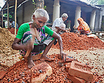 Mini Minjee breaks bricks for use in construction in the village of Suihari in northern Bangladesh. Severe floods in August 2017 damaged homes and swept away animals and crops in this neighborhood and across the region. Christian Aid and the Christian Commission for Development Bangladesh, both members of the ACT Alliance, worked together to provide emergency food packages to Minjee and other vulnerable residents of the affected area.
