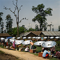Local residents with their new solar cookers during a cooking competition at a Bhutanese refugee settlement. All the entrants were given a solar cooker to take home with them after the event and the winner received a pressure cooker. With the financial help of the Dutch Council for Refugees, a total of 6,300 solar cookers will be distributed amongst the Bhutanese refugees living in the region. The solar cookers consist of a reflective, aluminium, parabolic-shaped device that concentrates the sun's rays onto cooking pots placed on a frame in the centre of the dish. The dish has to be adjusted to the new position of the sun around every 10 minutes. It takes about 55 minutes to prepare a cooked meal on a sunny day and it is hoped that using the solar cookers will alleviate pressure on resources and reduce kerosene consumption by 75%...