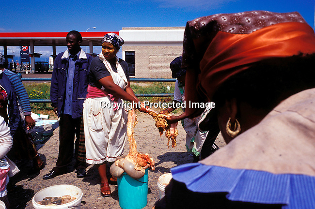 disbven00008.Digital. Small Business. Vendors. Women selling cow intestines (tripe) close to Nonqubela train station on November 4, 2003 in Site C Khayelitsha. It's popular for making traditional food. Plastic buckets, afval, informal trade. .©Per-Anders Pettersson/iAfrika Photos