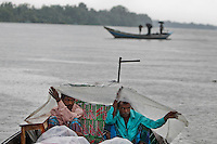 Bangladeshi boatmen shelter themselves with a plastic sheet as it rains on the Kaliganga River on the outskirts of Dhaka, Bangladesh.