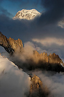 Needle with No Name and other craggy peaks in the foreground with Mont Blanc rising 4807 meters above the ground shrouded in morning fog and clouds in the background.